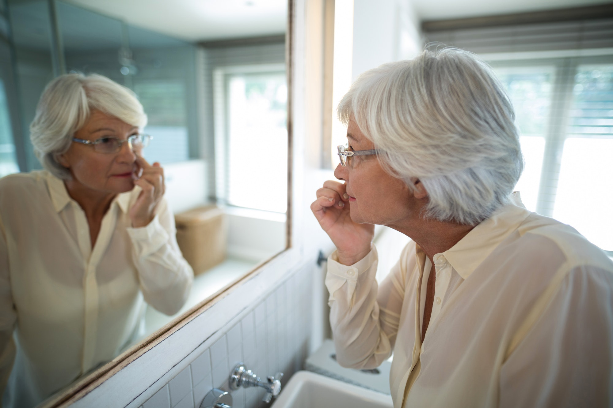 Senior woman checking her skin in mirror