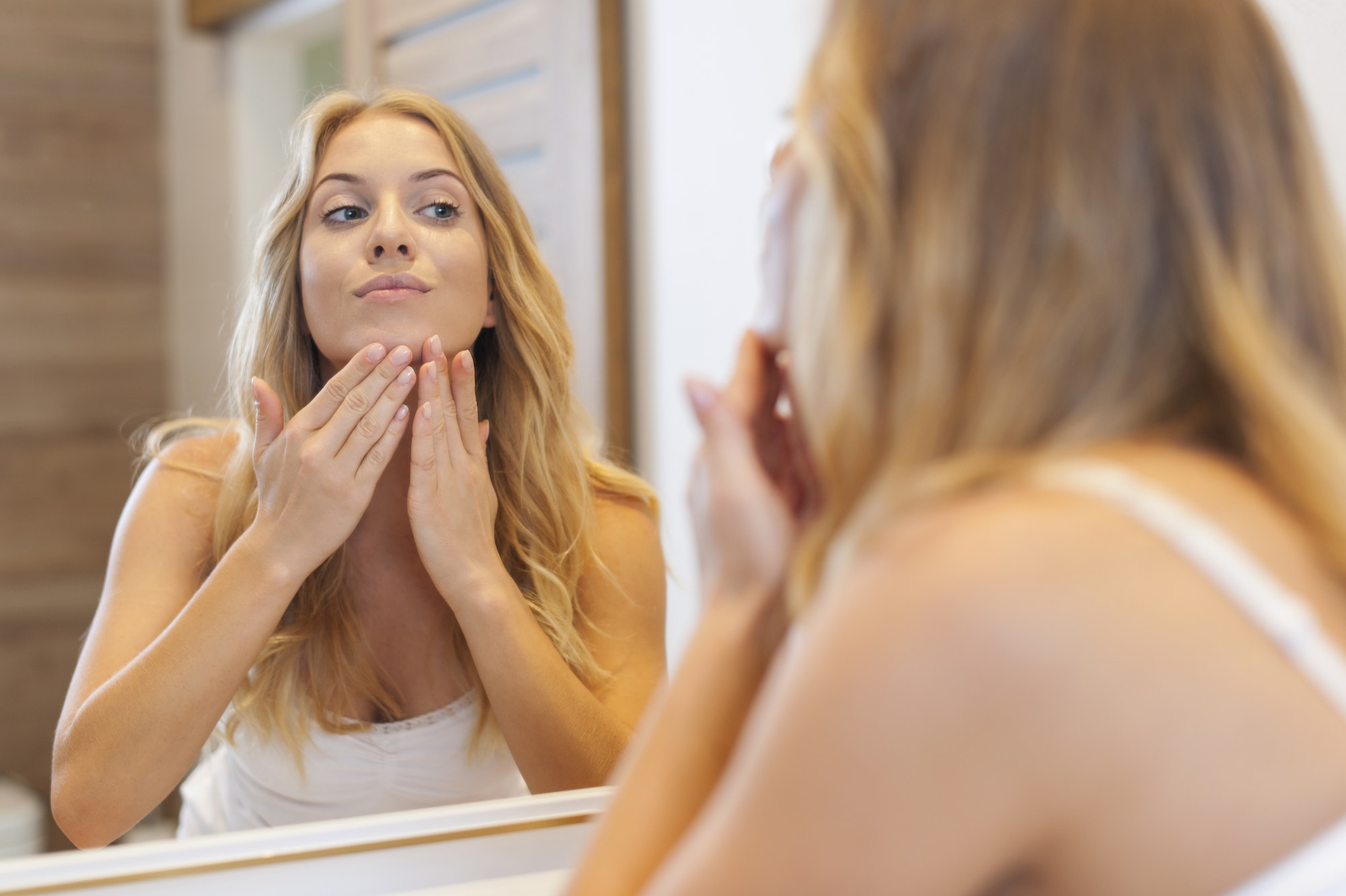 Blonde woman caring about her skin on face