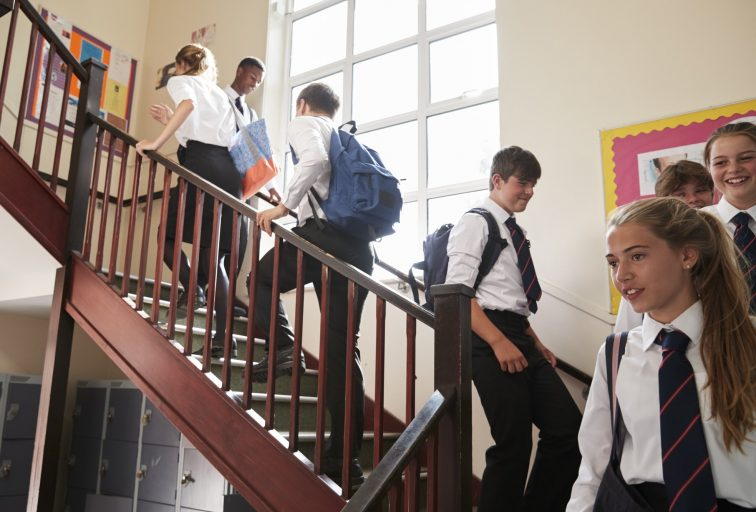 Group Of Teenage Students In Uniform Walking Between Classrooms