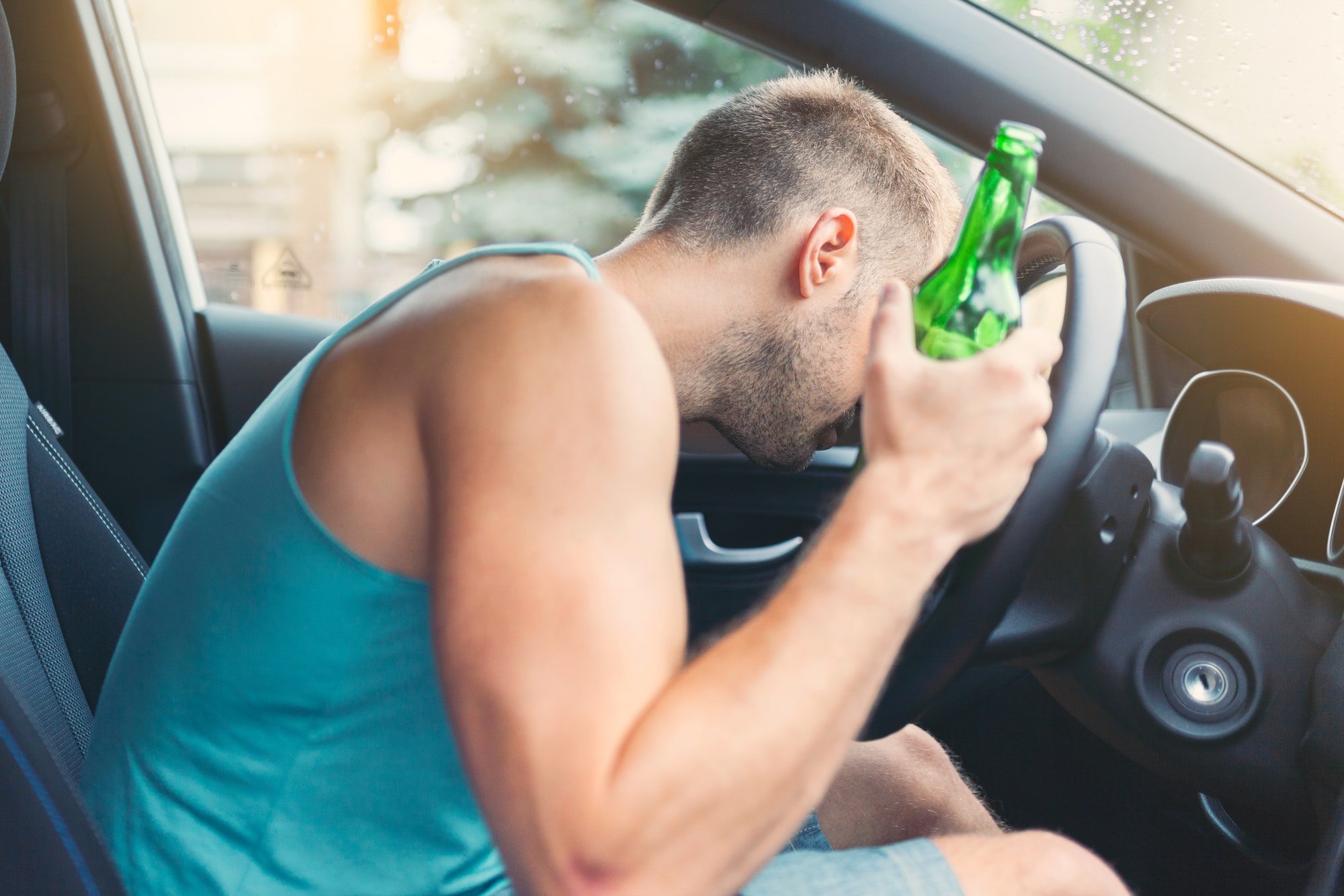 Drunk driver behind the steering wheel of a car