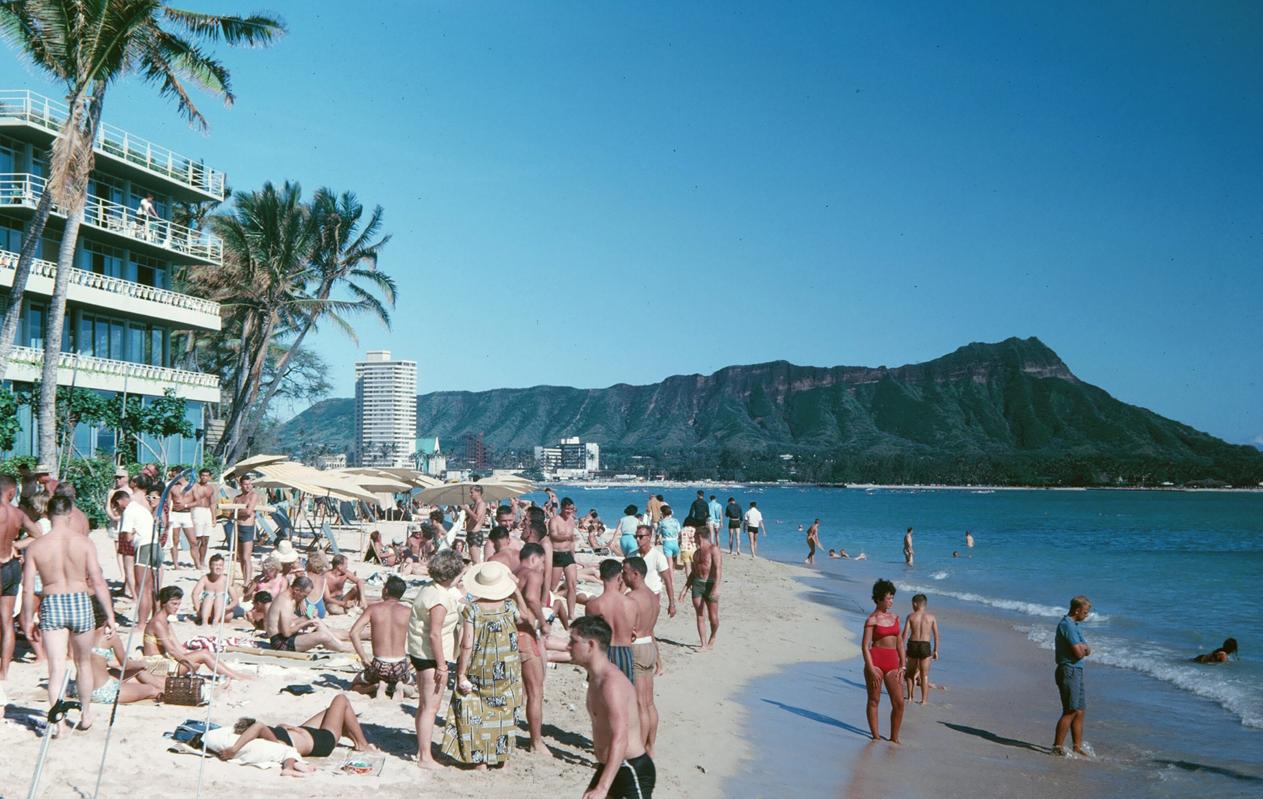 people on beach near seaside resort viewing mountain during daytime