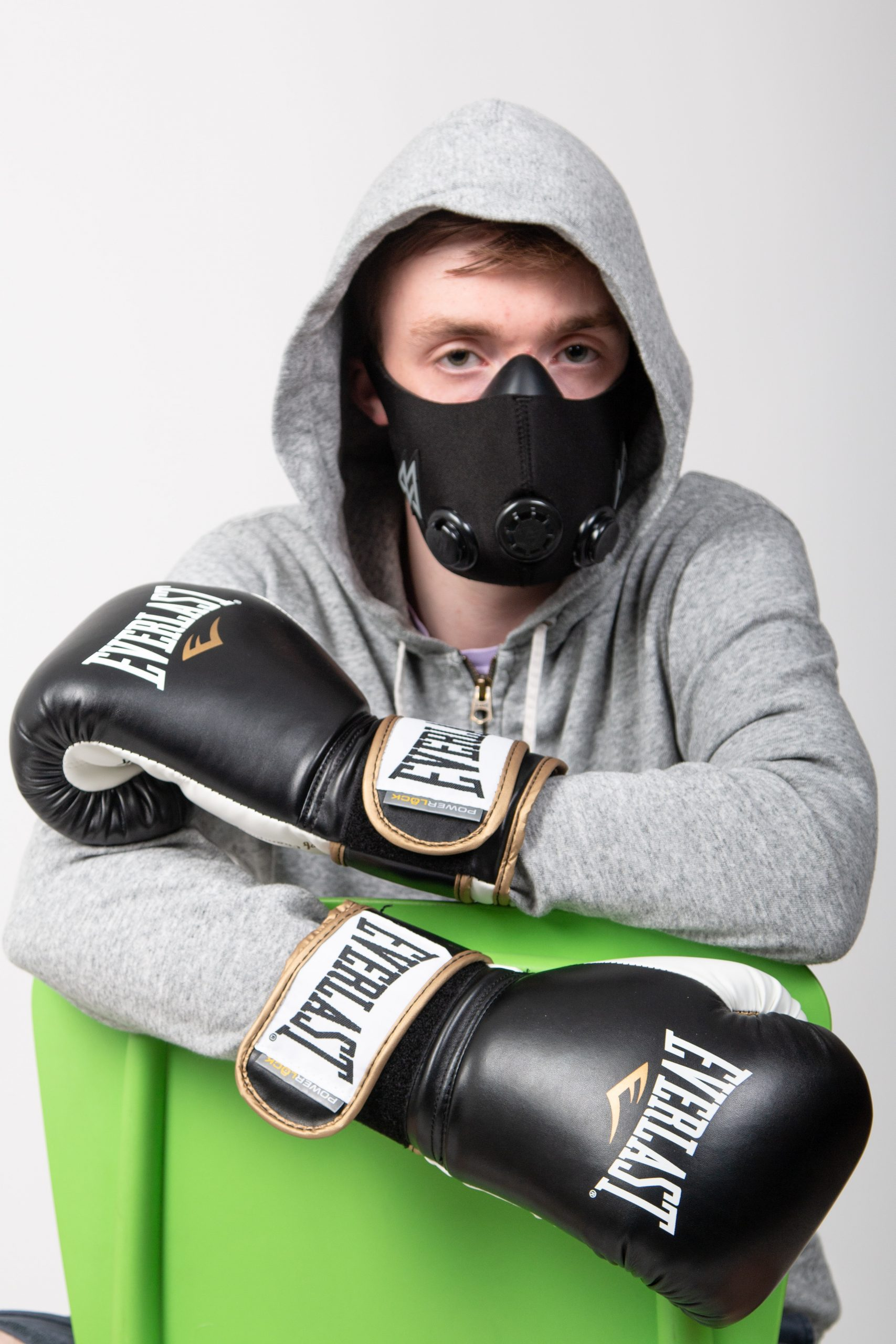man sits with face mask and black punching gloves